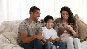 Family watching television on the sofa
