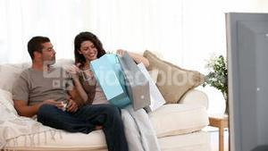 Man watching television when his wife comes home after shpping