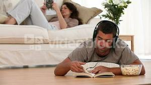 Man listening to music reading and lying on the floor while his wife looking at a magazine
