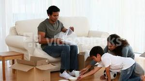 Lovely family unpacking boxes during their removal