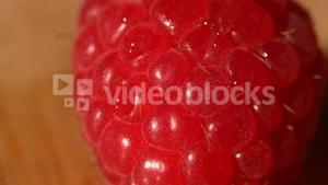 Water pouring over a raspberry