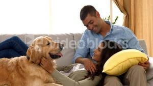 Happy couple with their dog at home