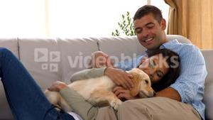 Happy couple with their puppy at home