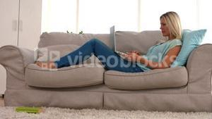 Happy blonde with laptop on sofa