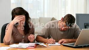 Couple calculating their bills together in the livingroom