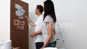 Couple painting wall in white