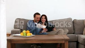 Happy couple looking at a tablet