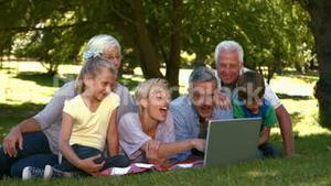 Happy family with laptop in park