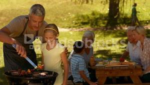 Happy family having barbecue in the park