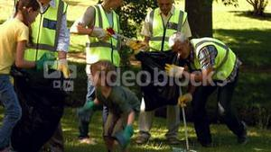 Active family collecting rubbish in park