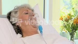 Woman lying on the bed with an oxygen mask