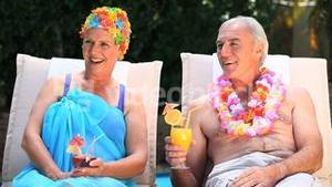 Old man and woman relaxing near the pool.