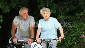 Elderly couple walking with their bikes