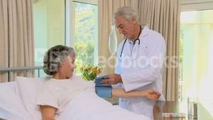 Old doctor measuring blood pressure at his female patient