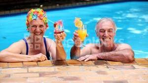 Happy old couple relaxing in the swimming pool