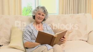 Old woman looking to an album and smiling at the camera