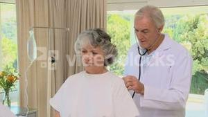 Old doctor examining a old patient