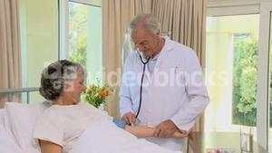 Doctor examining blood pressure of a old woman