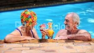 Seniors toasting with cocktails in the pool