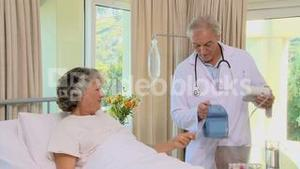 Old doctor checking his patients blood pressure