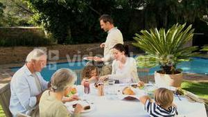 Family and grandparents having barbecue in the garden