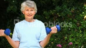 Elderly woman working her muscles with dumbbells