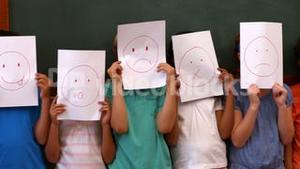 Pupils holding pages with faces