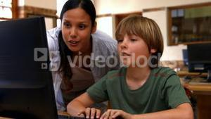 Pupil and teacher in computer class at school