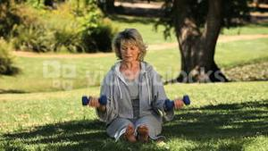 Elderly woman working her muscles with dumbbells sitting on the grass