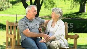 Elderly couple sitting on a bench and talking
