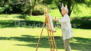 Old woman painting a canvas