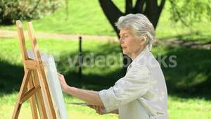 Elderly female painting a canvas