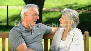 Old man talking with his wife on a bench