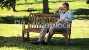Old man talking on the phone on a bench