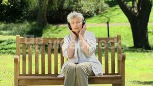 Old woman listening to music with headset on a bench