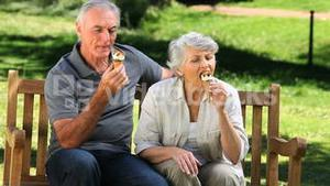 Old man enjoying icecream with his wife on a bench