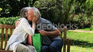 Old man looking at clothes with his wife after shopping on a bench