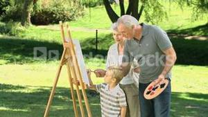 Grandparents and grandson painting a canvas