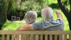 Old man relaxing with his wife on a bench