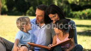 Family reading a book sitting on the grass