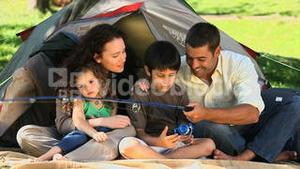 Cute family fishing in front of the tent