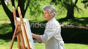 Old female painting a canvas