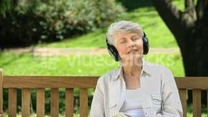 Old female listening to music with headset on a bench