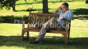 Old male talking on the phone on a bench
