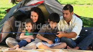 Happy family fishing in front of the tent