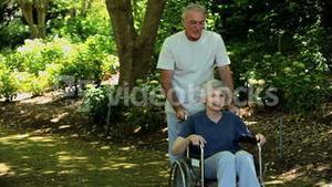 Man strolling with a woman in a wheelchair