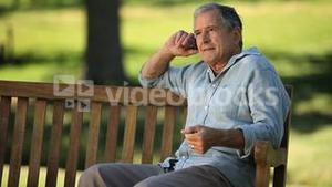 Senior man talking on the phone on a bench