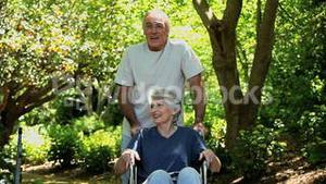 Man strolling with his wife in a wheelchair