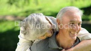 Close up of a old woman hugging her husband sitting on a bench