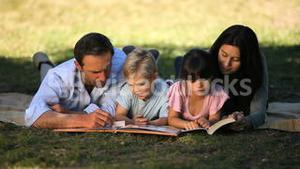 Family reading a book lying on a tablecloth